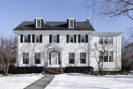 house exterior: Suburban home in winter with black shutters