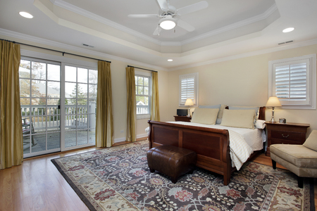master bedroom: Master bedroom with tray ceiling and deck view Stock Photo
