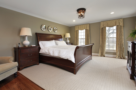 master bedroom: Master bedroom in luxury home with dark wood bedframe Stock Photo