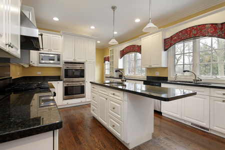 Kitchen in remodeled home with white cabinetry