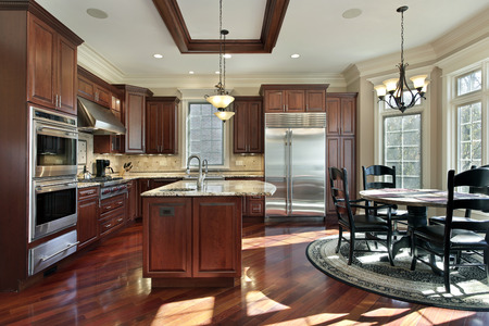 lightings: Luxury kitchen with cherry wood cabinetry and eating area