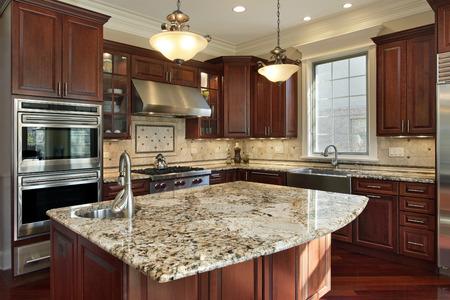 Cocina con isla de granito y gabinetes de madera de cerezo Foto de archivo