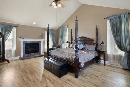 Master bedroom in suburban home with fireplace