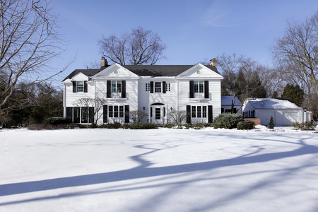 Suburban home in winter with detached garage