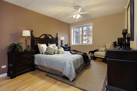 master: Master bedroom in condominium with dark wood furniture