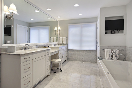 lighting fixtures: Master bath in suburban home with white cabinetry Stock Photo