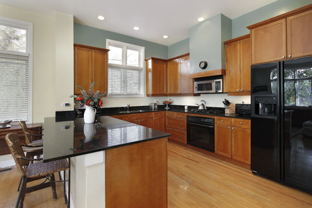 Kitchen with breakfast bar and wood cabinetry Stock Photo