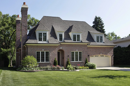 Brick home in suburbs with two chimneys Standard-Bild