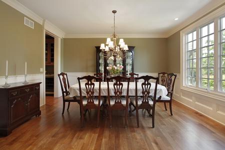 familia cenando: Comedor en casa suburbana con paredes de oro