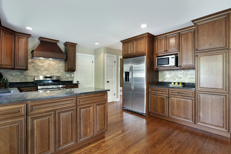 furnishings: Kitchen in suburban home with oak wood cabinetry Stock Photo