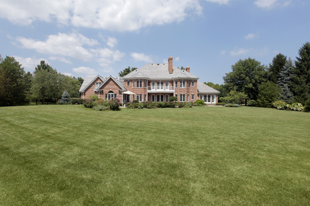 Rear view of luxury brick home with expansive yard. Stock Photo