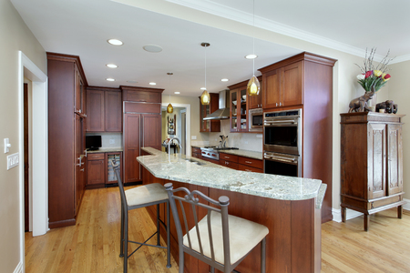 Modern kitchen with double decker island and cherrywood cabinetry. Stockfoto
