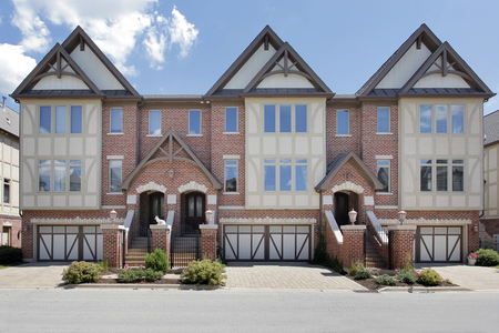 Row of tudor style brick townhouses with front gates. Stock Photo
