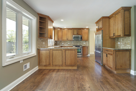 Kitchen in remodeled home with oak wood cabinetry.