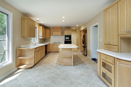 kitchen island: Kitchen in remodeled home with center island and oak wood cabinetry. Editorial