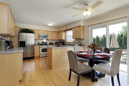 furnishings: Kitchen in suburban home with eating area and doors to patio.