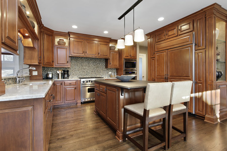 cabinetry: Kitchen in luxury home with oak wood cabinetry and center island.