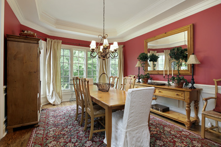 Dining room in luxury home with red walls.