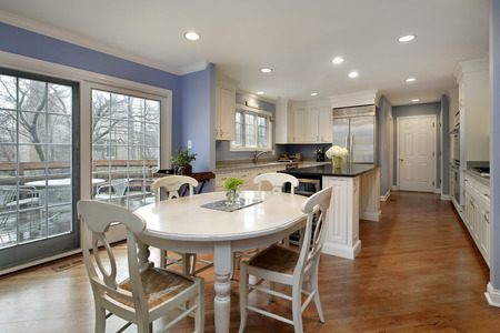 Kitchen in suburban home with white cabinetry and white table.