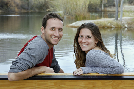 Happy young couple sitting on a bench swing beside a lake.