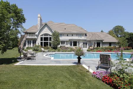Zwembad in achterkant van luxe huis met blauw stenen terras. Stockfoto