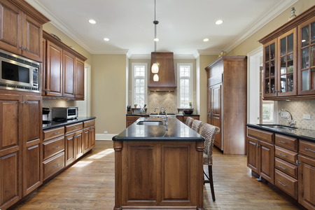 kitchen furniture: Kitchen in luxury home with black granite island top.