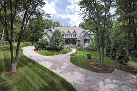 Aerial view with a drone of an upscale home with front porch in a suburban setting.