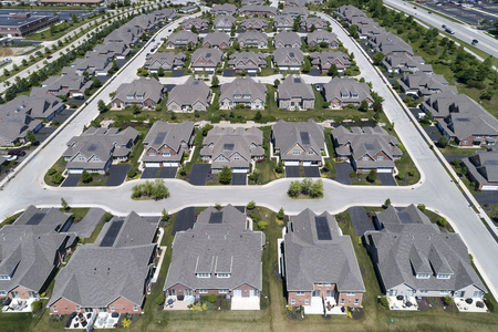 zoned: Aerial view of a townhouse complex in a semi-circular Chicago suburban neighborhood in summer.