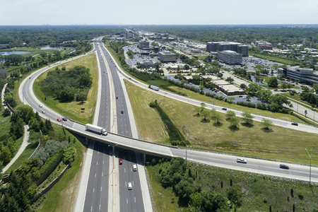 turnpike: Aerial view of a highway and ramp with cars and trucks in a Chicago suburban setting.