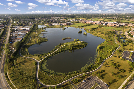 townhomes: Aerial view of a lake and peninsula near a community center and townhomes with walking paths and bridge in The Glen, Glenview, Illinois.