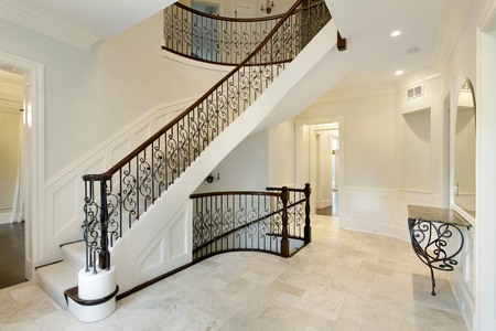Foyer in suburban home with wrought iron staircase railing. Foto de archivo