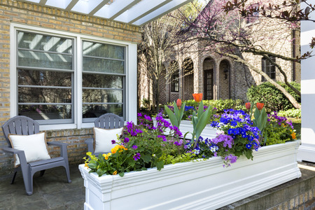Variety of flowers in a flower pot with deck chairs on a front porch of a suburban home. Reklamní fotografie