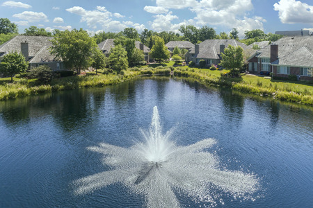 Aerial view of a townhouse complex with a pond and fountain in a Chicago suburban neighborhood in summer. Stock Photo