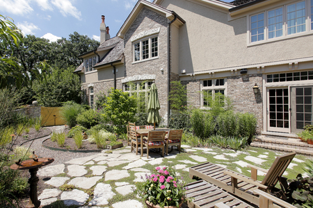 Patio of upscale home with stone steps and gravel. Reklamní fotografie