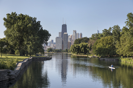 A man rowing a scull along the South Lagoon in Lincoln Park with downtown Chicago in the distance. USA Stock Photo