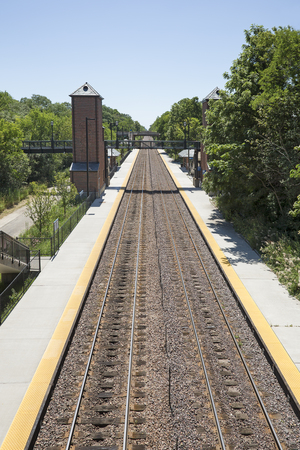 Train tracks at a suburban train station with bridge.
