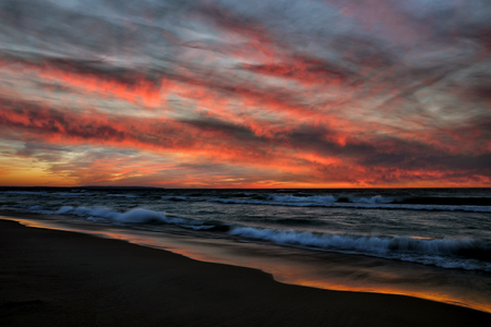 Dramatic sunset with waves and a ribbon of colorful water along Esch Beach in Sleeping Bear National Lakeshore in Michigan. USA Reklamní fotografie