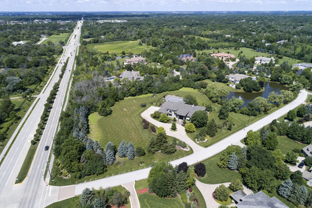 Aerial view of a luxury neighborhood with mature trees and a pond in a Chicago suburban neighborhood in summer. Bannockburn, IL. USA