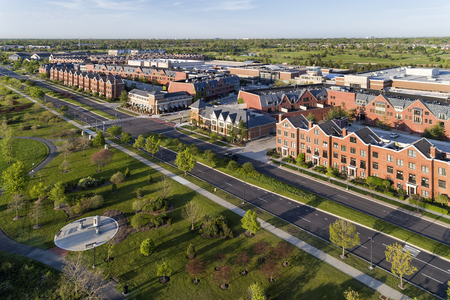 Aerial view of a restaurants and a row of townhouses along Patriot Bouldevard in the Glen in Glenview, Illinois just after sunrise.