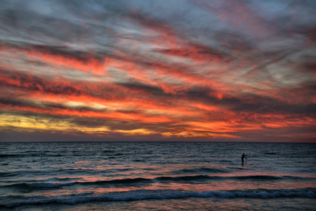 Stand-up paddleboarder surfing the waves of Lake Michigan at the public beach in Frankfort, Michigan under a dramatic sunset. USA Reklamní fotografie