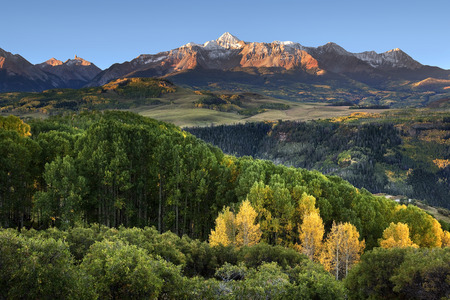 Wilson Peak in the Colorado Rockies near Telluride with a stand of yellow aspens and rolling hills in the distance just after dawn Фото со стока