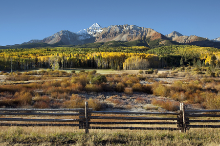 Wilson Peak in the Colorado Rockies near Telluride with yellow and green aspens and rail fence just after sunrise Reklamní fotografie