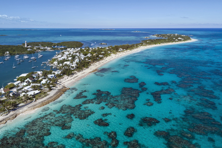 Aerial view of the harbour, lighthouse and beach in Hope Town on Elbow Cay off the island of Abaco, Bahamas.