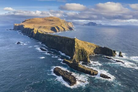 Aerial view of a lighthouse, dramatic cliffs and crashing waves along the island of Mykines in the Faroe Islands Reklamní fotografie