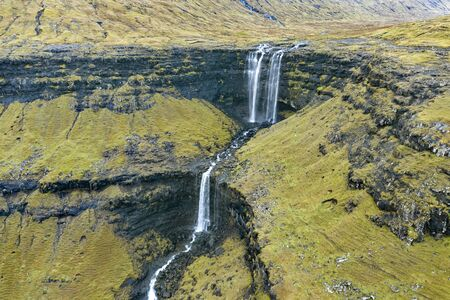 Aerial view of Fossa Waterfall, the highest waterfall in the Faroe  Islands. This double-tiered waterfall is 459 feet high and cascades down into the sea. Reklamní fotografie