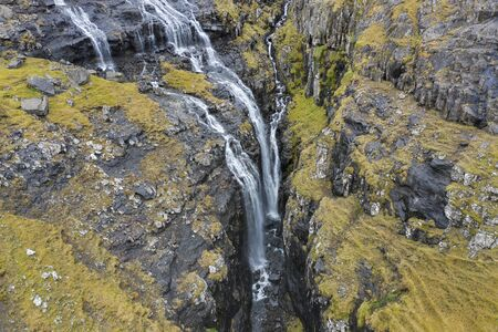 Aerial view of waterfalls and cascades along a rocky ridge and narrow gorge near the village of Tjornuvik on the island of Streymoy in the Faroe Islands.