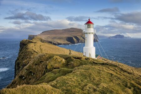 View of the Holmur Lighthouse on the island of Mykines in the Faroe Islands.