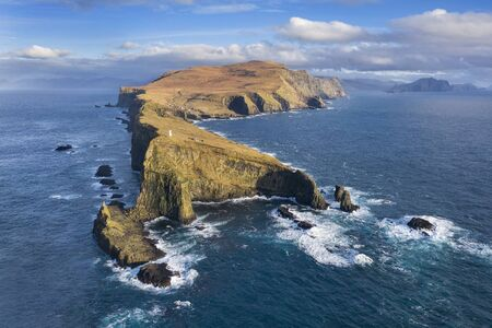 Aerial view of a lighthouse, dramatic cliffs and crashing waves along the island of Mykines in the Faroe Islands. Reklamní fotografie