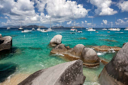 Boulders dot the shoreline of the Baths with boats moored in the distance at the Baths on Virgin Gorda in the British Virgin Islands. Stock Photo