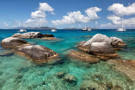 Boulders dot the waters of the Baths with boats moored in the distance at the Baths on Virgin Gorda in the British Virgin Islands. Stock Photo